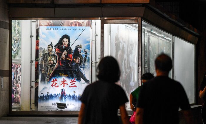 People walk past a poster of the Disney movie 'Mulan' outside a cinema in Beijing on Sept. 10, 2020. (Greg Baker/AFP via Getty Images)