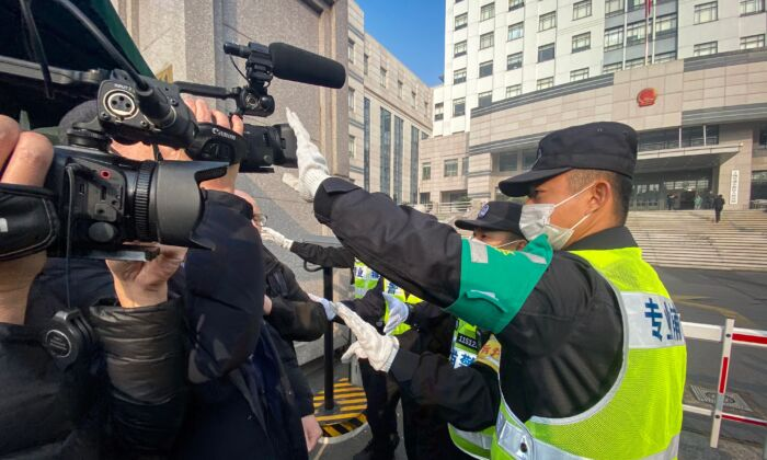 A policeman covers a camera to stop a journalist from recording footage outside the Shanghai Pudong New District People's Court in Shanghai, China, on December 28, 2020. (Leo Ramirez/AFP via Getty Images)