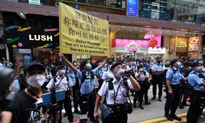 Police hold up a warning banner and instruct people to move on during the 24th anniversary of Hong Kong's handover from Britain to Chinese rule in Hong Kong on July 1, 2021. (Peter Parks/AFP via Getty Images)