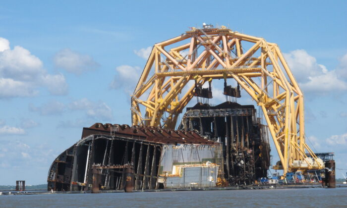 A towering crane pulls the engine room section away from the remains of the capsized cargo ship Golden Ray, offshore of St. Simons Island, Ga. on April 26, 2021. (Russ Bynum/AP Photo)