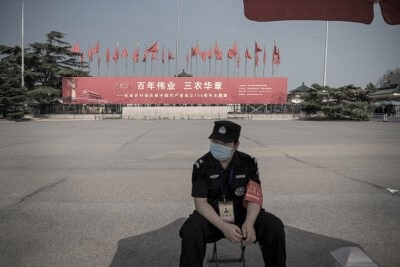 A guard sits in front of the Agricultural Exhibition Center where a sign celebrating the upcoming centenary of the Communist Party of China is seen in Beijing, on June 28, 2021. (Andrea Verdelli/Getty Images)