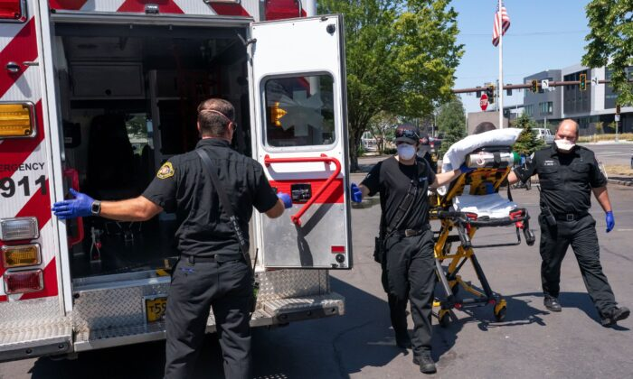 Salem Fire Department paramedics and employees of Falck Northwest ambulances respond to a heat exposure call during a heat wave in Salem, Ore., on June 26, 2021. (Nathan Howard/AP Photo)