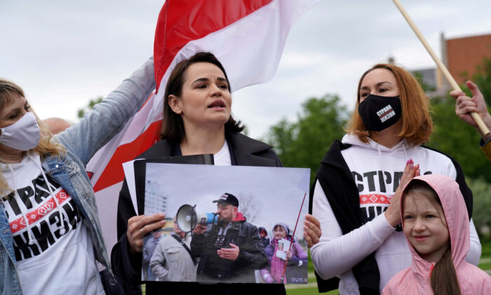"""Belarus opposition leader Sviatlana Tsikhanouskaya holds a picture of her husband Syarhei Tsikhanouski during a """"Belarus support day"""" protest in Vilnius, Lithuania, on May 29, 2021. (Janis Laizans/Reuters)"""