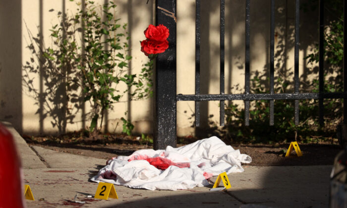 A blood-soaked sheet sits among evidence markers following a shooting where three people were shot at the Wentworth Gardens housing complex in the Bridgeport neighborhood in Chicago, Illinois, on June 23, 2021. (Scott Olson/Getty Images)
