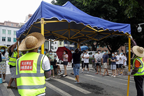 Volunteers set up a tent as residents prepare to receive nucleic acid tests for COVID-19 in Guangzhou in China's southern Guangdong province, on May 30, 2021. (STR/AFP via Getty Images)