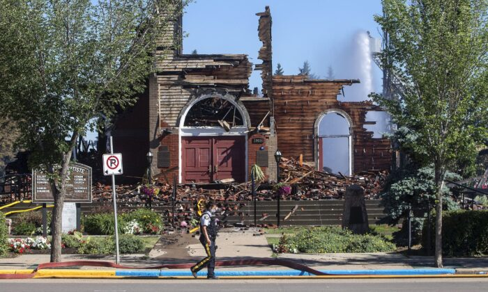 A police officer walks past what's left of St. Jean Baptiste Parish Catholic church in Morinville, Alta., after it was burned down on June 30, 2021. (The Canadian Press/Jason Franso)
