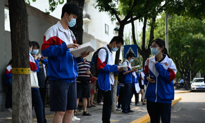 """Mask-clad students conduct last-minute studying before sitting for the second day of the National College Entrance Examination (NCEE), known as """"gaokao"""", in Beijing on July 8, 2020.  According to """"China's 2020 Fertility Report"""" published by the Evergrande Research Institute, on average, education was 32.44 percent of the total expenditure for Chinese families in 2020, showing a rising trend. (Photo by WANG ZHAO/AFP via Getty Images)"""