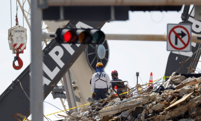 Rescue personnel continue the search and rescue operation for survivors at the site of a partially collapsed residential building in Surfside, Fla., on July 2, 2021. (Marco Bello/Reuters)