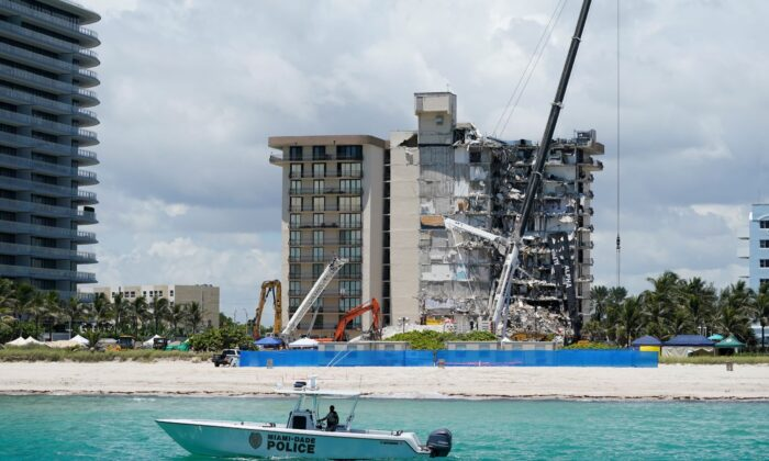 A Miami-Dade County Police boat patrols in front of the Champlain Towers South condo building, where search and rescue efforts continue more than a week after the building partially collapsed, in Surfside, Fla., on July 2, 2021. (Mark Humphrey/AP Photo)