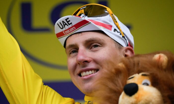 Slovenia's Tadej Pogacar, wearing the overall leader's yellow jersey, celebrates on the podium after the eighth stage of the Tour de France cycling race over 150.8 kilometers (93.7 miles) with start in Oyonnax and finish in Le Grand-Bornand, France, on July 3, 2021. (Christophe Ena/AP Photo)
