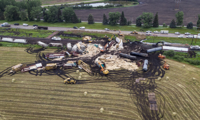 Crews work to clean up a spill after the derailment of a 20-car train carrying tar sands and lumber near Blackfalds, Alberta, Canada, on July 3, 2021. (Jeff McIntosh/The Canadian Press via AP)