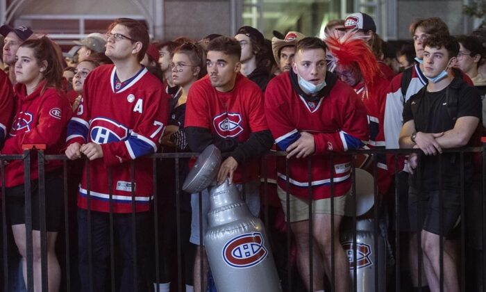 Montreal Canadiens fans look on outside the Bell Centre in Montreal, on July 2, 2021, during game 3 of the NHL Stanley Cup final against the Tampa Bay Lightning. (The Canadian Press/Graham Hughes)