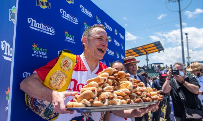 Winners Joey Chestnut and Michelle Lesco, obscured behind hot dogs, pose at the Nathan's Famous Fourth of July International Hot Dog-Eating Contest in Coney Island's Maimonides Park in the Brooklyn borough of New York City, on July 4, 2021. (Brittainy Newman/AP Photo)