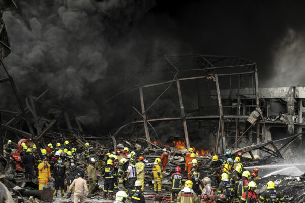 Firefighters work at the site of a massive explosion