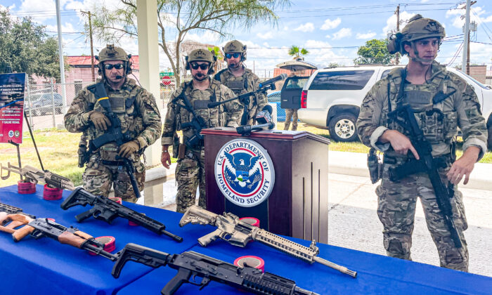 Law enforcement agents stand behind seized weapons bound for Mexico during a press conference in Laredo, Texas, on July 2, 2021. (Charlotte Cuthbertson/The Epoch Times)
