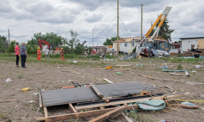 People survey the damage to homes following a Tornado in Mascouche, Que., on June 22, 2021. (The Canadian Press/Graham Hughes)