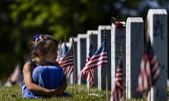 A girl sits in the grass among the headstones of those killed during the  wars in Iraq and Afghanistan in Section 60 of Arlington National  Cemetery in Arlington, Va., during Memorial Day on May 31, 2021.  (Samuel Corum/Getty Images)