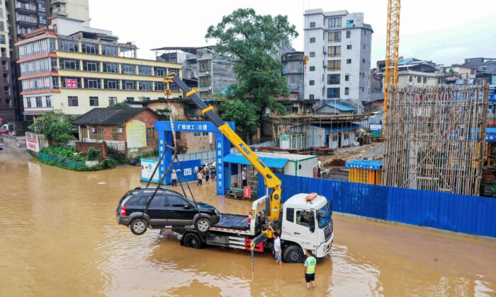 A crane lifts a car on a flooded street near the swollen Rongjiang river after heavy rains in Rongan, in China's southern Guangxi region on July 2, 2021. - China OUT (Photo by STR / AFP) / China OUT (Photo by STR/AFP via Getty Images)