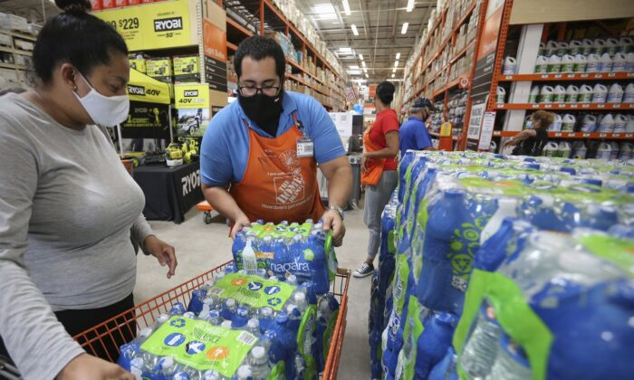 Home Depot department supervisor, Arnaldo Gonzalez, loads water bottles into Elena Arvalo's shopping cart as shoppers prepare for possible effects of tropical storm Elsa in Miami, Fla., on July 3, 2021. (Al Diaz/Miami Herald via AP)