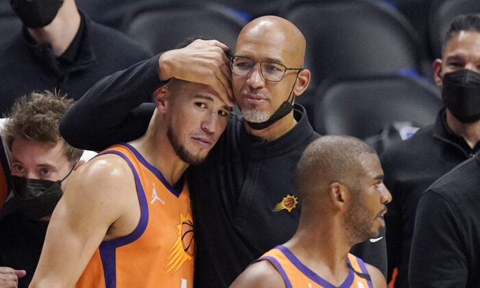 Phoenix Suns head coach Monty Williams, center, hugs Devin Booker, left, as Chris Paul stands by as time runs out in Game 6 of the NBA basketball Western Conference Finals in Los Angeles, Calif., on June 30, 2021. (Mark J. Terrill/AP Photo)