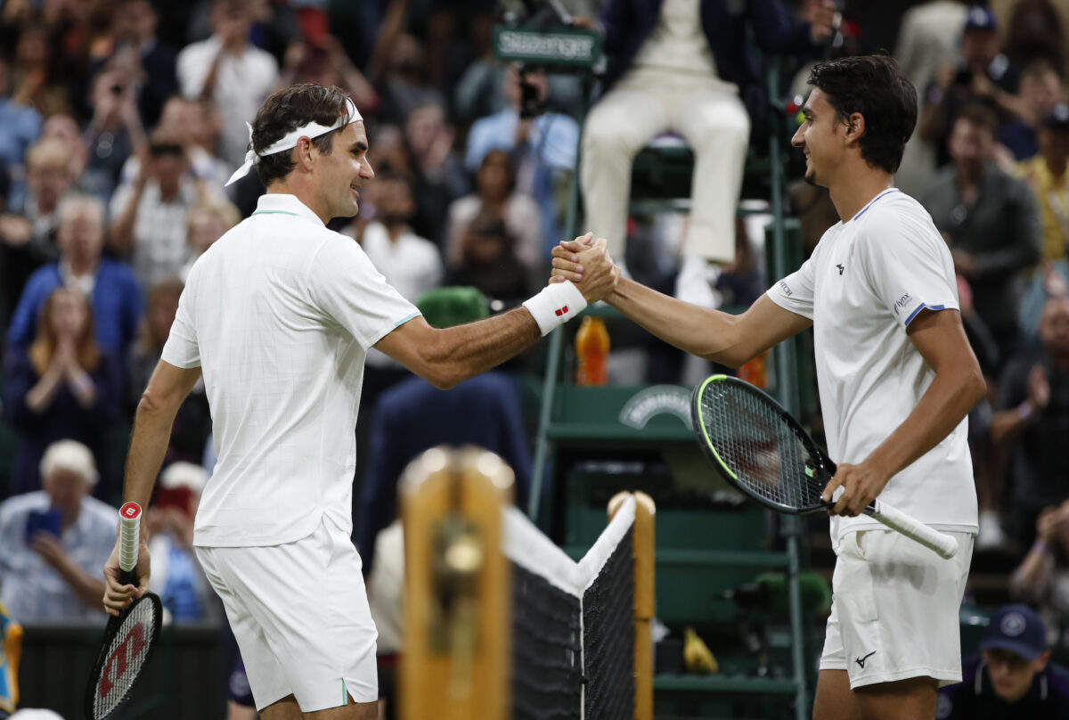 Switzerland's Roger Federer shakes hands with Italy's Lorenzo Sonego