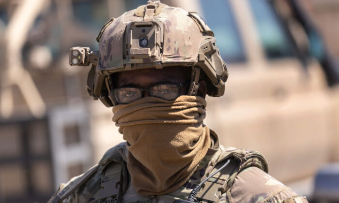 A U.S. Army soldier stands guard as his commanding officer and allied troops meet with local villagers on May 26, 2021 near the Turkish border in northeastern Syria.(John Moore/Getty Images)