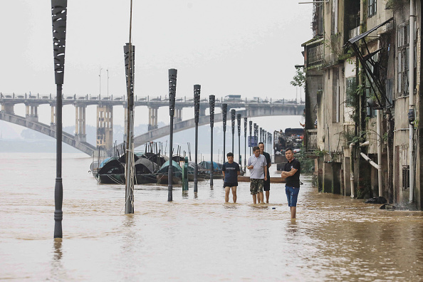 People walk along the swollen Rongjiang river after heavy rains in Rongan, in China's southern Guangxi region, on July 2, 2021. (STR/AFP via Getty Images)