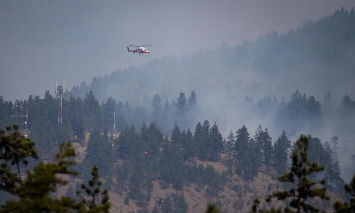 A helicopter pilot prepares to drop water on a wildfire burning in Lytton, B.C., on July 2, 2021. (The Canadian Press/Darryl Dyck)