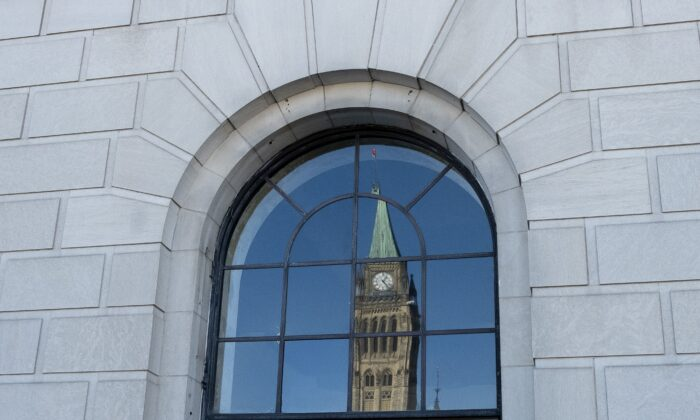 The Peace Tower on Parliament Hill is reflected in a window in downtown Ottawa on March 26, 2019. (The Canadian Press/Adrian Wyld)