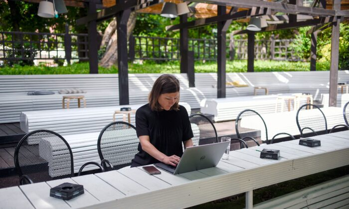 A project manager works on her computer in a cafe in a file photo. (Nikolay Doychinov/AFP via Getty Images)