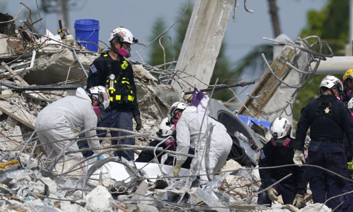 Search and rescue team members climb the rubble of the Champlain Towers South condo in Surfside, Fla., on July 7, 2021. (Al Diaz/Miami Herald via AP)