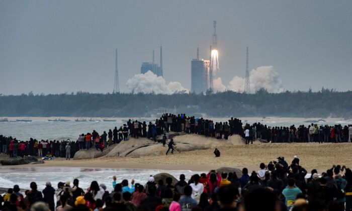 People watch the Long March 8 rocket, the latest in China's Long March launch vehicle fleet, as it lifts off from the Wenchang Space Launch Center in southern China's Hainan Province on Dec. 22, 2020. (STR/AFP via Getty Images)