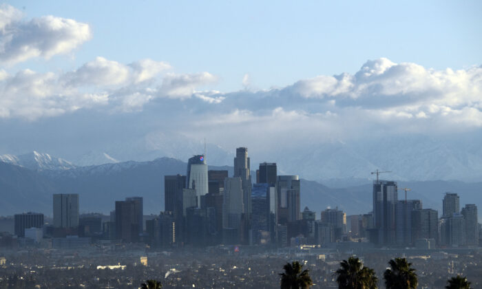 Snow-topped mountains stand behind the Los Angeles downtown skyline after sunrise in Los Angeles on Dec. 29, 2020. (Patrick T. Fallon/AFP via Getty Images)