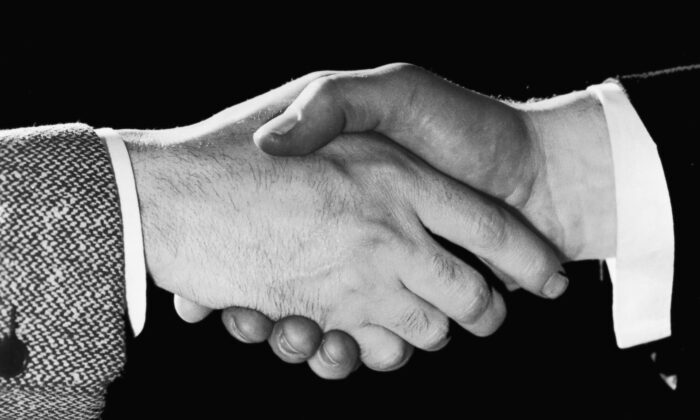 A close-up of two men shaking hands, in a file photo. (FPG/Hulton Archive/Getty Images)