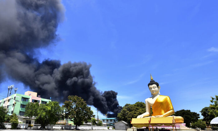 Rising smoke is seen behind the giant Buddha statue in Samut Prakan province, Thailand, on July 5, 2021. (AP Photo)