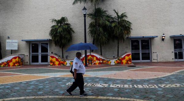 A man walks with an umbrella ahead of Tropical Storm Elsa