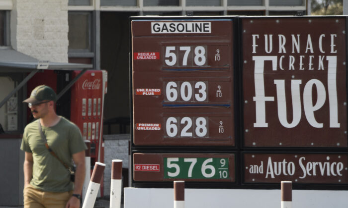 A pedestrian walks past gas station fuel prices above $5 and $6 per gallon at Death Valley National Park in Furnace Creek, Calif., on June 17, 2021. (Patrick T. Fallon/AFP via Getty Images)