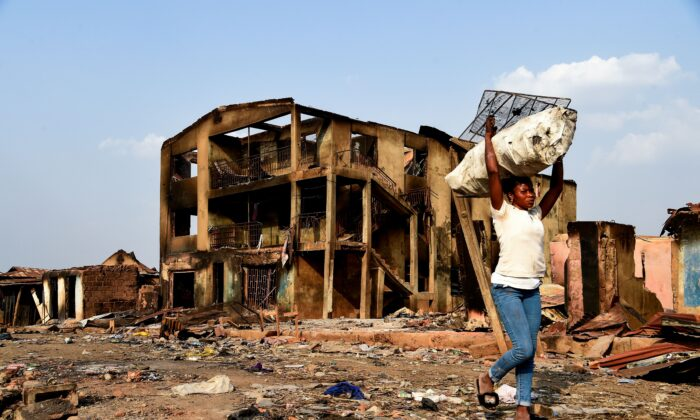 A woman carries wares recovered from burned shops as she walks past a three-story building burned during deadly clashes with the northern Fulani at Shasha Market in Ibadan, southwest Nigeria, on Feb. 15, 2021. (Pius Utomi Ekpei/AFP via Getty Images)