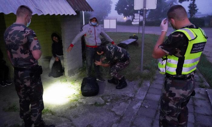 Lithuanian border guards detain migrants on Lithuania-Belarus border in Kalviai, Lithuania, on July 7, 2021. (Janis Laizans/Reuters)