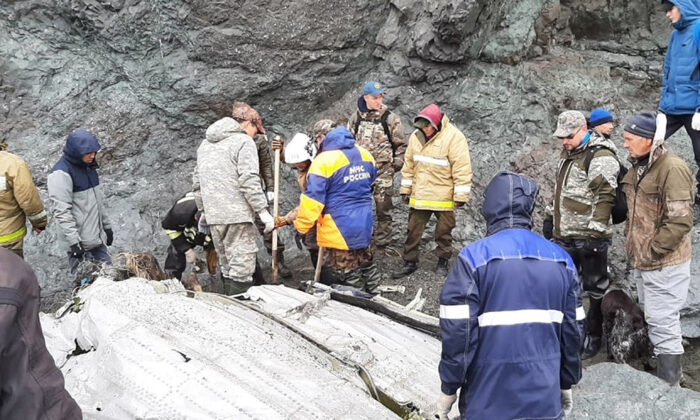 Russia Emergency Situations Ministry workers at the wreckage of a missing Antonov An-26 plane found near its destination airport outside the town of Palana, in Russia's Far East on Wednesday, July 7, 2021. (Russia Emergency Situations Ministry press service via AP)