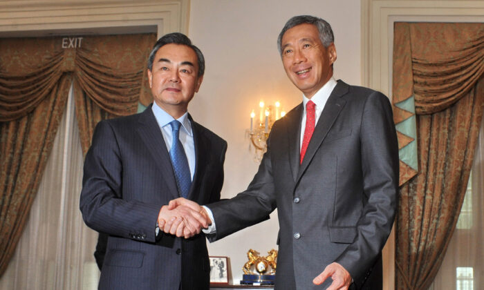 Chinese Foreign Minister Wang Yi (L) shakes hands with Singaporean Prime Minister Lee Hsien Loong (R) during a call at the Istana presidential palace in Singapore on May 3, 2013. Wang is on a two-day visit in Singapore, his first official visit as foreign minister. (Mohd Fyrol/AFP via Getty Images)