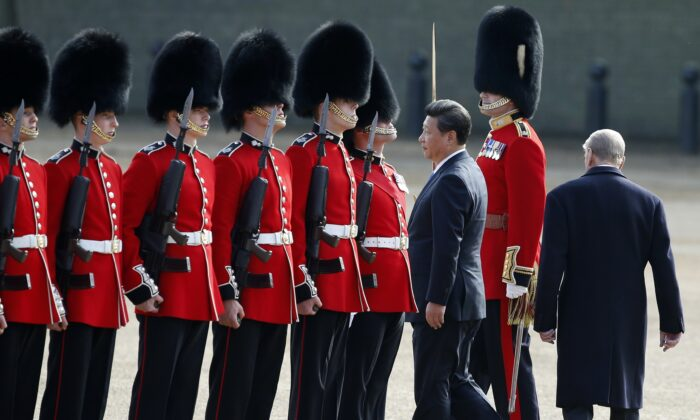 Chinese leader Xi Jinping (L) inspects the guard of honour on Horse Guards Parade in central London on Oct. 20, 2015 during the ceremonial welcome for Xi Jinping and his wife Peng Liyuan on the first official day of a state visit. (Alastair Grant/AFP via Getty Images)