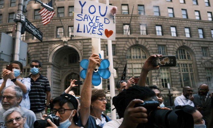 People cheer as hundreds of police, fire, hospital and other first responder workers and essential workers participate in a ticker tape parade along the Canyon of Heroes to honor the workers who helped navigate New York through COVID-19 in New York City on July 7, 2021. (Spencer Platt/Getty Images)