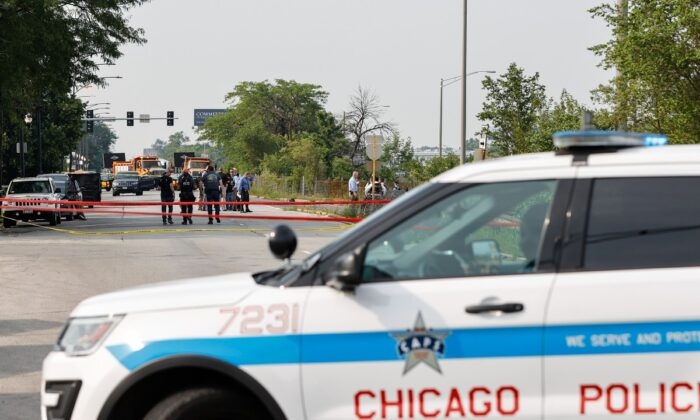 Law enforcement officers investigate the crime scene near the border between the Morgan Park and West Pullman neighborhoods in Chicago, Ill., on July 7, 2021. (Kamil Krzaczynski/Getty Images)