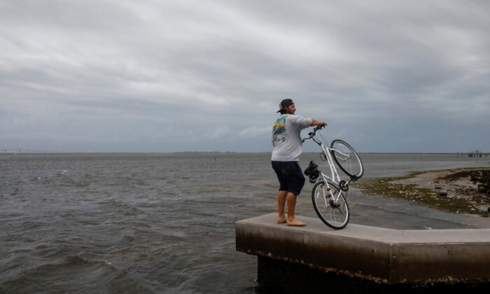 A man holds his bicycle at Bay Vista Park, as Elsa strengthened into a Category 1 hurricane hours before an expected landfall on Florida's northern Gulf Coast, in St. Petersburg, Florida, on July 6, 2021. (Octavio Jones/Reuters)