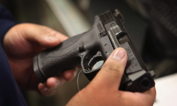 A customer shops for a pistol at Freddie Bear Sports sporting goods store in Tinley Park, Ill., on Dec. 17, 2012. (Scott Olson/Getty Images)