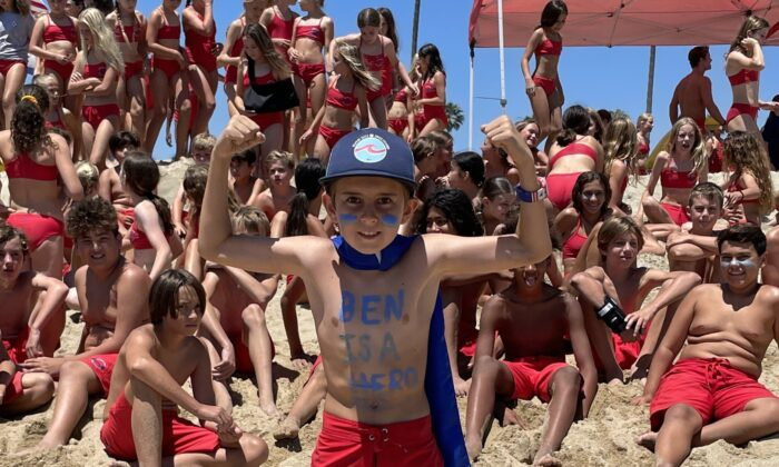 """""""Ben is a Hero"""" enthusiast and Newport Beach junior lifeguard Dylan Gabriele with fellow junior lifeguard participants during the July 6 Ben Carlson Day in Newport Beach, Calif. Carlson died July 6, 2014, while attempting to save a distressed swimmer. (Courtesy of Jake Janz)"""