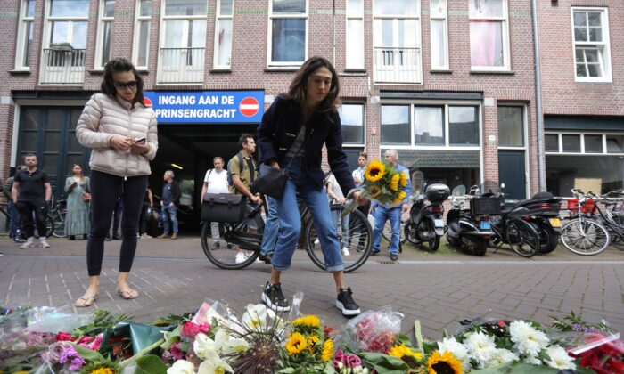A woman leaves flowers where Dutch celebrity crime reporter Peter R. de Vries was shot and reported seriously injured in Amsterdam on July 7, 2021. (Eva Plevier/Reuters)