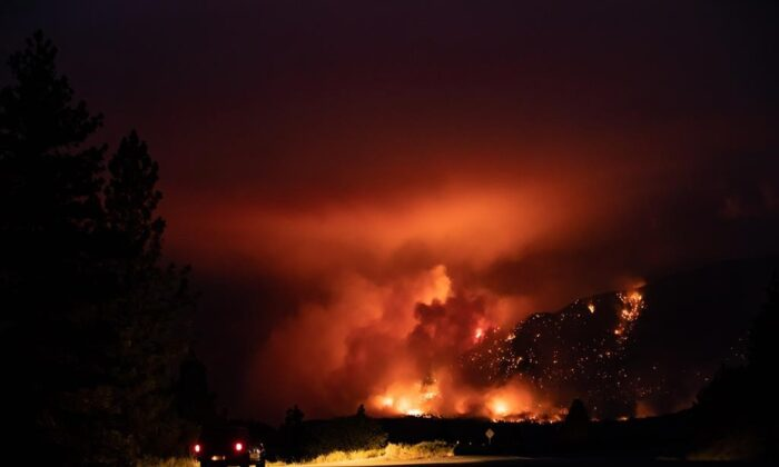 A motorist watches from a pullout on the Trans-Canada Highway as a wildfire burns on the side of a mountain in Lytton, B.C., on July 1, 2021. (The Canadian Press/Darryl Dyck)