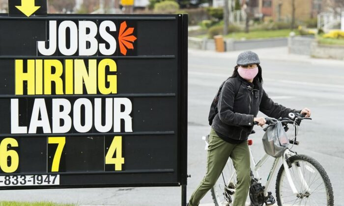 A woman checks out a jobs advertisement sign during the COVID-19 pandemic in Toronto on April 29, 2020. (The Canadian Press/Nathan Denette)